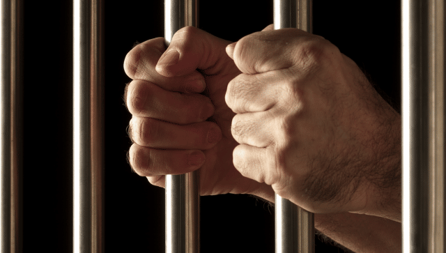 hands of a prisoner behind bars