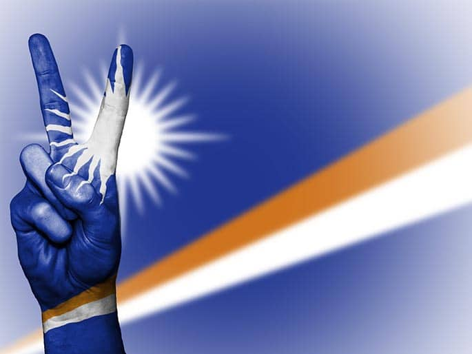 picture of the Marshall Islands flag with peach hand symbol to accomodate blog post about Marshall Island cryptocurrency