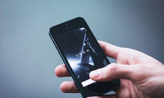 mobile phone with uber logo to accompany article about Uber's terms of service changes