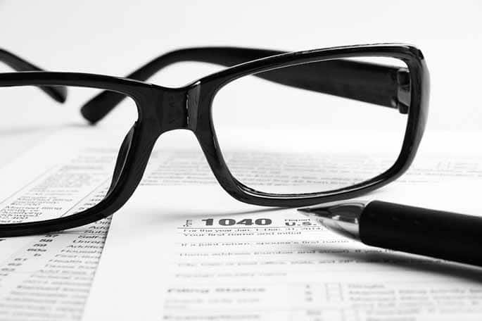 Picture of glasses on IRS form to accompany article about IRS tool to use social media to catch tax cheats
