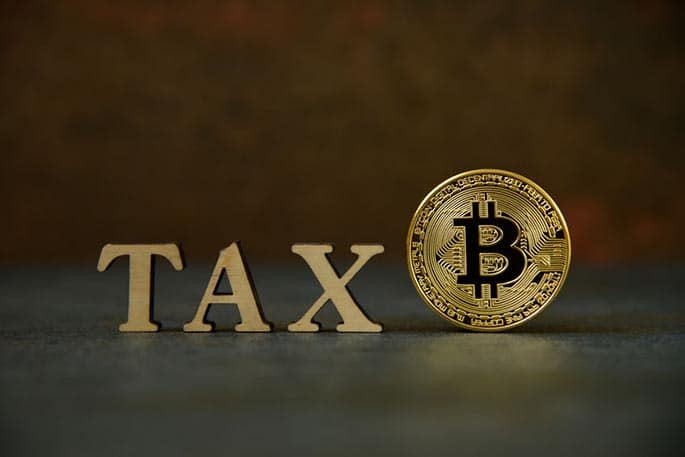 picture of a Bitcoin next to the word tax